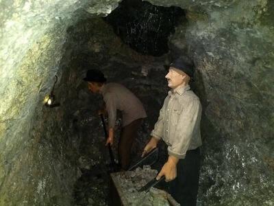 Slika lutk oblečenih v rudarje, kako ročno kopljejo rudo